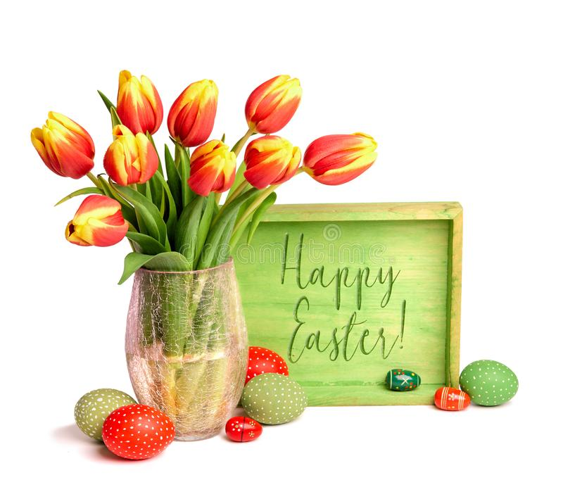 Red tulips with yellow tops and Easter eggs isolated on white ba. Ckground. Text `Happy Easter` on the green wooden board royalty free stock images