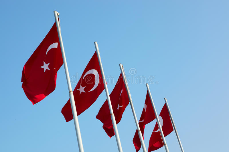 Red Turkish flags. Blowing in the wind on a clear blue sky day stock image