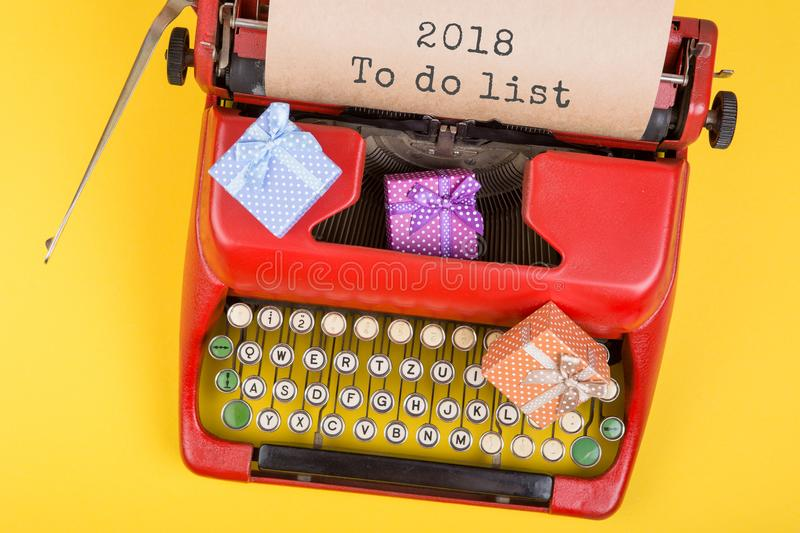 """Red typewriter with the text """"2018 To do list"""" and gift boxes on yellow background. Christmas concept - red typewriter with the text """"2018 To do stock image"""