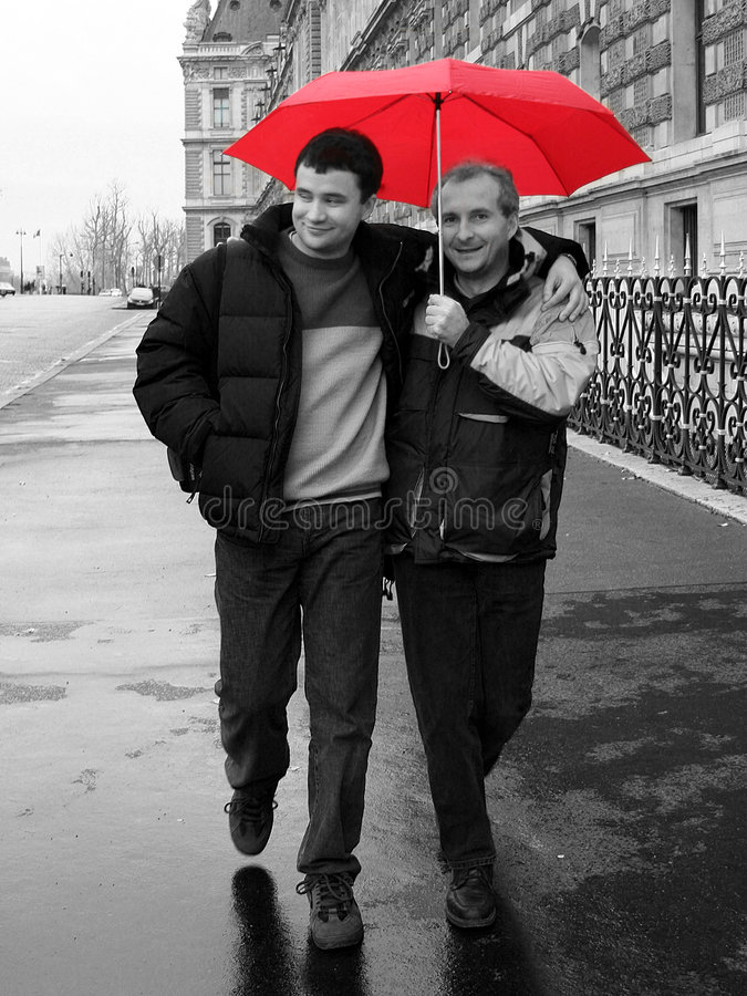 Red umbrella. 2 male friends walking on the street of Paris