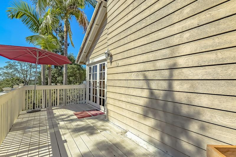 Red umbrella at the corner of the balcony of a house with wooden exterior wall. Lush trees can be seen against the clear blue sky on this sunny day stock photography