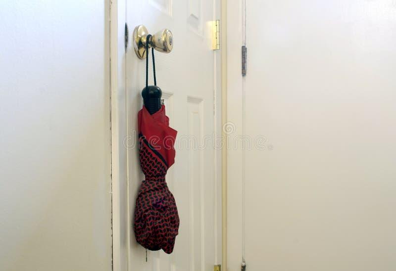 Red umbrella hanging on door knob. In white hallway royalty free stock photos