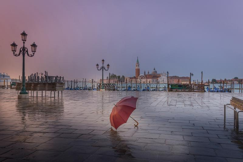 Red umbrella in rainy early morning in Venice royalty free stock photo