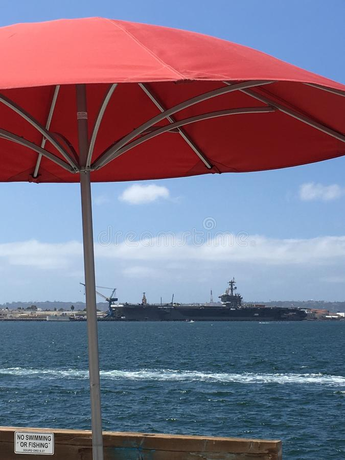 Red Umbrella. A red umbrella brightens the view with a United States carrier in the background royalty free stock photography