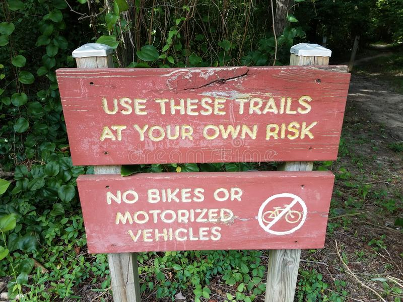 Red use these trails at your own risk sign and no bikes or motorized vehicles allowed sign near trail. A red use these trails at your own risk sign and no bikes stock photography