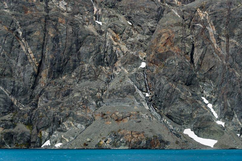 Red ut grå färger vaggar framsidan med orange och vita mineraliska åder, snölappar och is- blått vatten, den Drygalski fjorden, s royaltyfria bilder