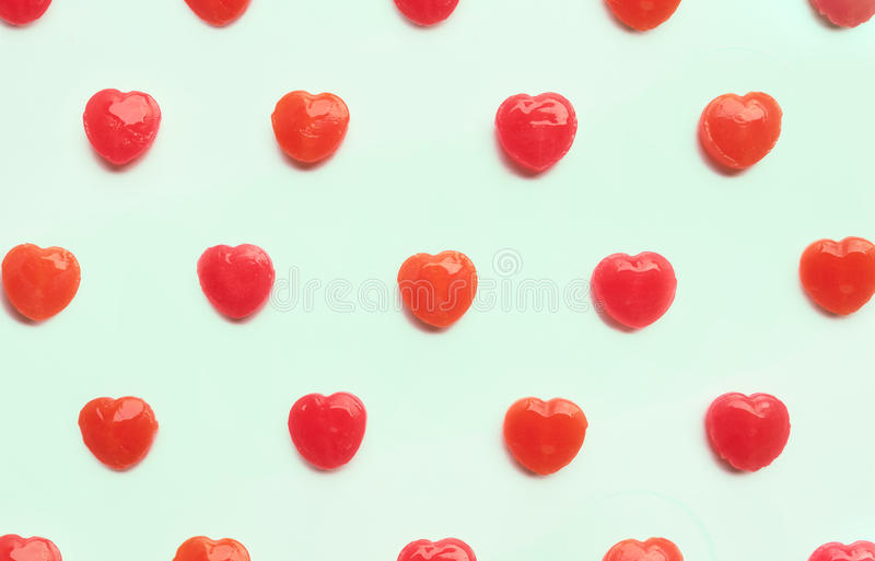 Red Valentine`s day heart candy pattern on green pastel paper color background. Love Concept. colorful hipster style. top view. stock images