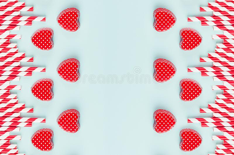 Red valentines and striped straws on mint color paper as decorative abstract festive background for Valentine`s day. stock photos
