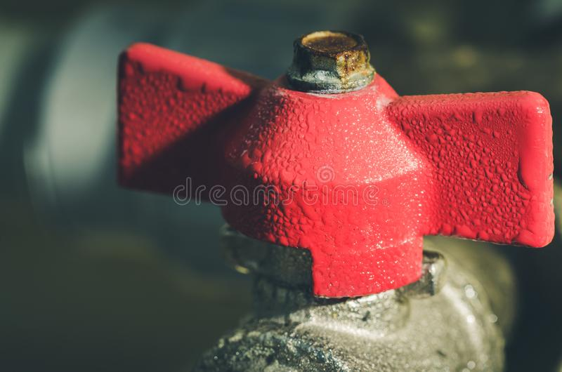 Red valve on a pipe/crane with the gate for water. Toned stock images