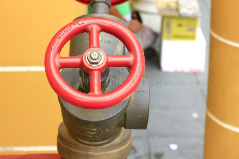 Red Valves for Fire Extinguishers. Brass pipe with red valve for supplying fire water on the road royalty free stock image