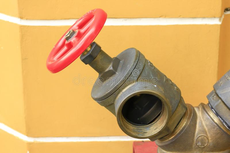Red Valves for Fire Extinguishers. Brass pipe with red valve for supplying fire water on the road stock images