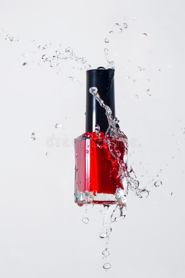 Red varnish in water splashes stock photo