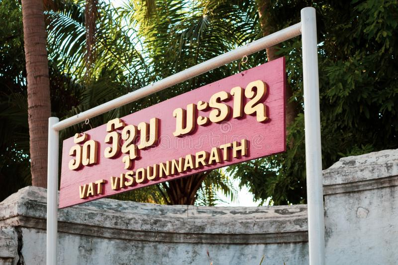 Red Vat Visounnarath signboard on the road. Wooden signboard of Vat Visounnarath, one of the Buddha complexes in Luang Prabang which is the UNESCO World Heritage stock photo