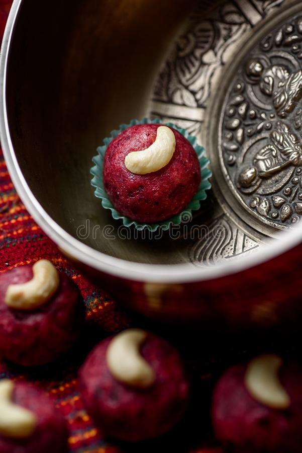 Red vegan candy with nuts, raw food truffles, decorated with cashew nuts on a beautiful silver plate. Close-up stock photography