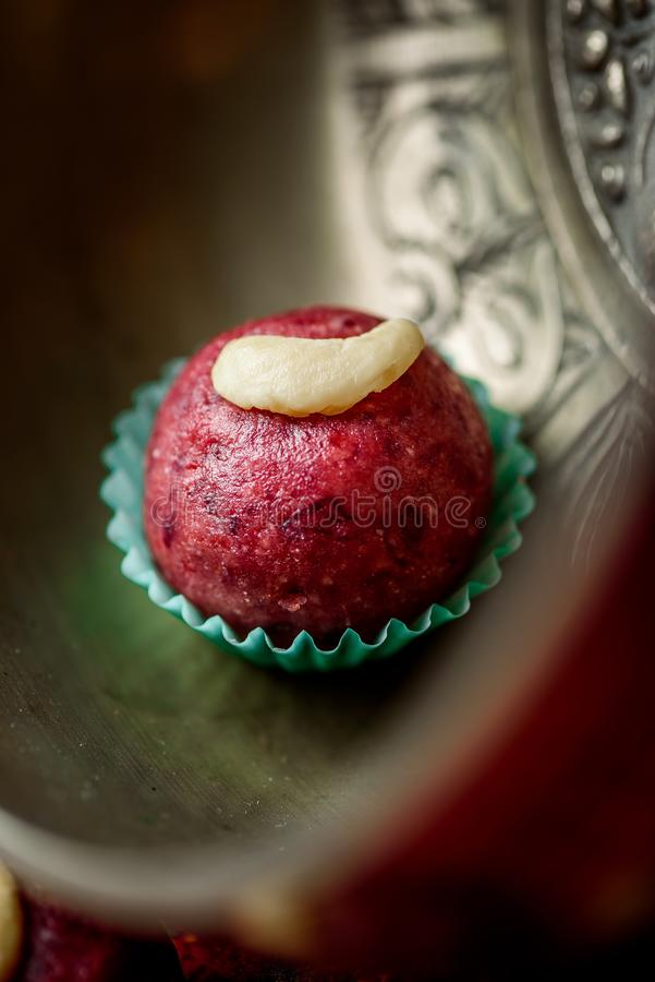 Red vegan candy with nuts, raw food truffles, decorated with cashew nuts on a beautiful silver plate. Close-up royalty free stock photo