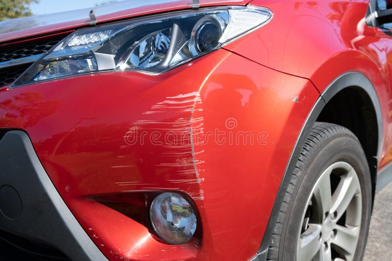 Red vehicle bumper deeply scratched. Red vehicle bumper deeply scratched closeup stock image