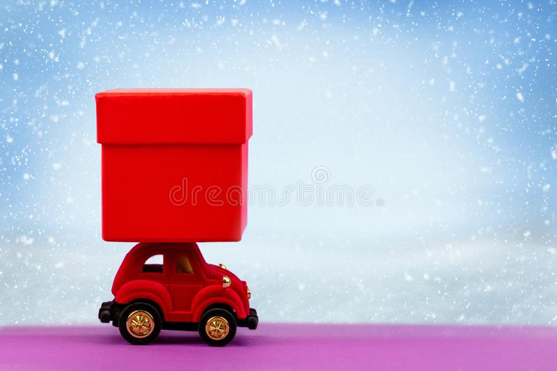 Red velour toy car with red gift box for Christmas, new year, Valentine`s day, birthday on winter snow background. Background with copy space stock image
