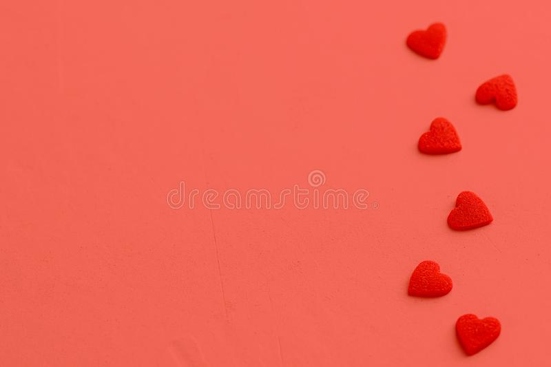 Red velure texture heart candies scattered on coral background. Border frame arrangement. Valentine romance mother`s day charity stock photos