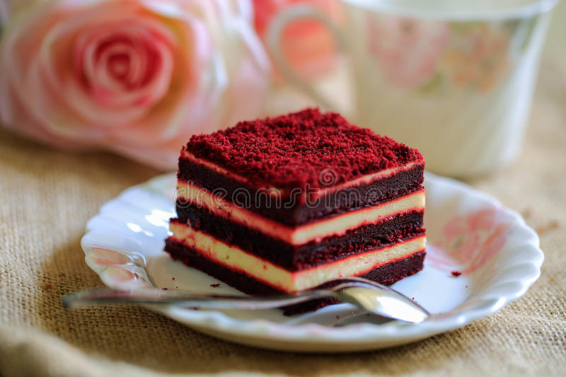 Red velvet cake with beautiful cup of tea on brown cloth background stock photography