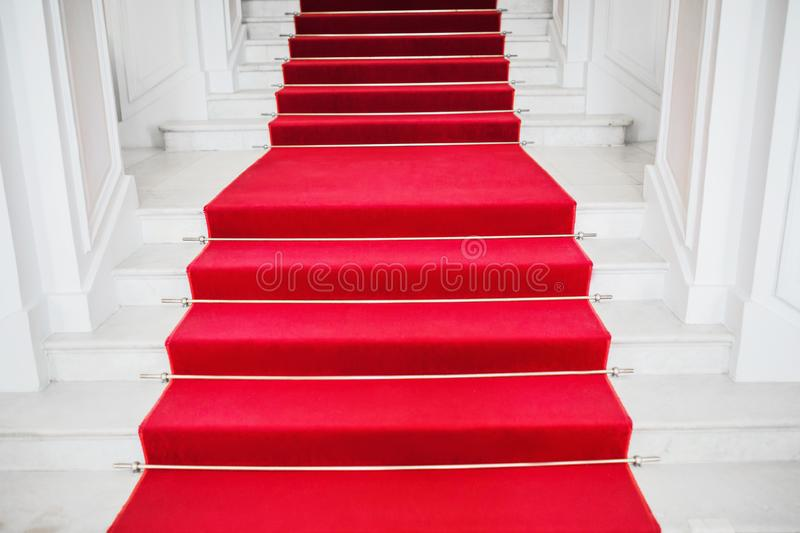 Red velvet carpet. Climb the stairs. Prestigious nomination. Stairway go up. Business success. Stairs covered with red carpet. stock photo