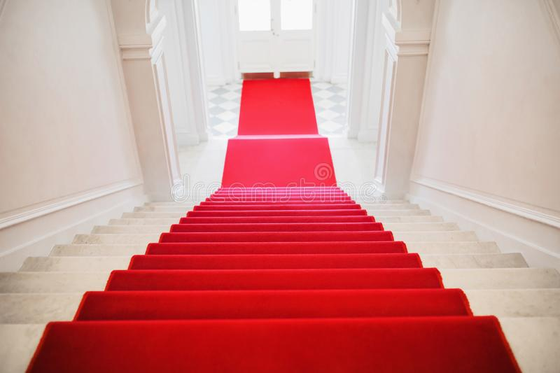Red velvet carpet. Stairs go down. Corridor with entrance. Prestigious nomination. Way to failure. Exit to street. Business crash. Stairs covered with red stock photo