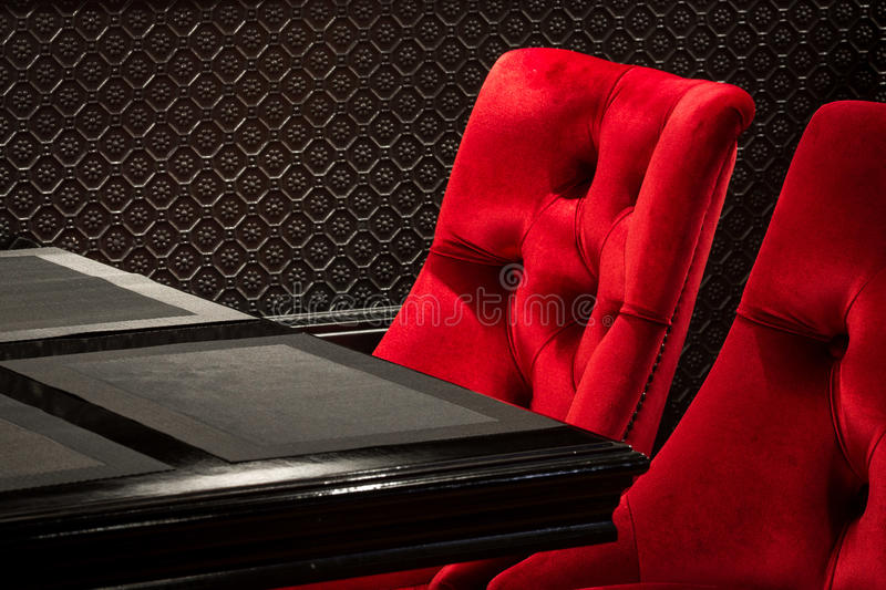Red velvet chairs and black table. Red velvet chairs and table black, elegant piece of interior of restaurant royalty free stock photo
