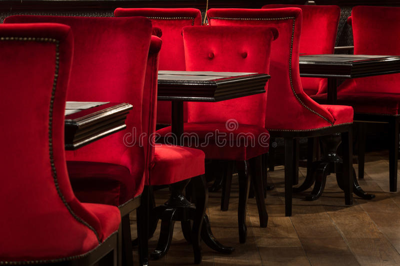 Red velvet chairs and black tables stock photo