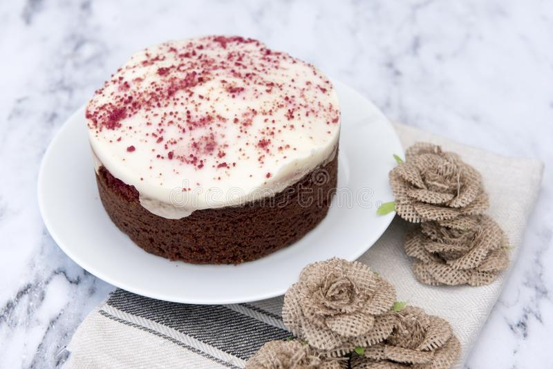Red velvet cheesecake, decorated with hessian flowers royalty free stock photo
