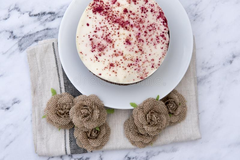 Red velvet cheesecake, decorated with hessian flowers royalty free stock image