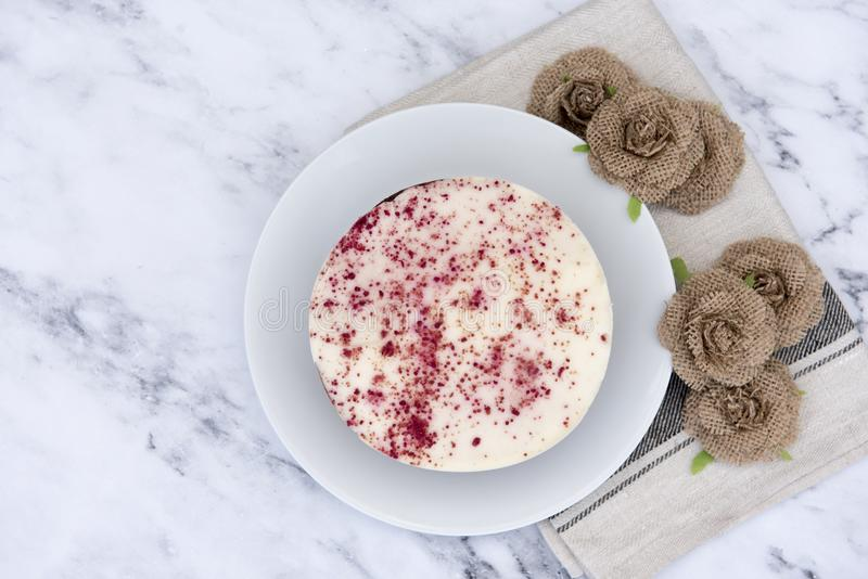 Red velvet cheesecake, decorated with hessian flowers stock images