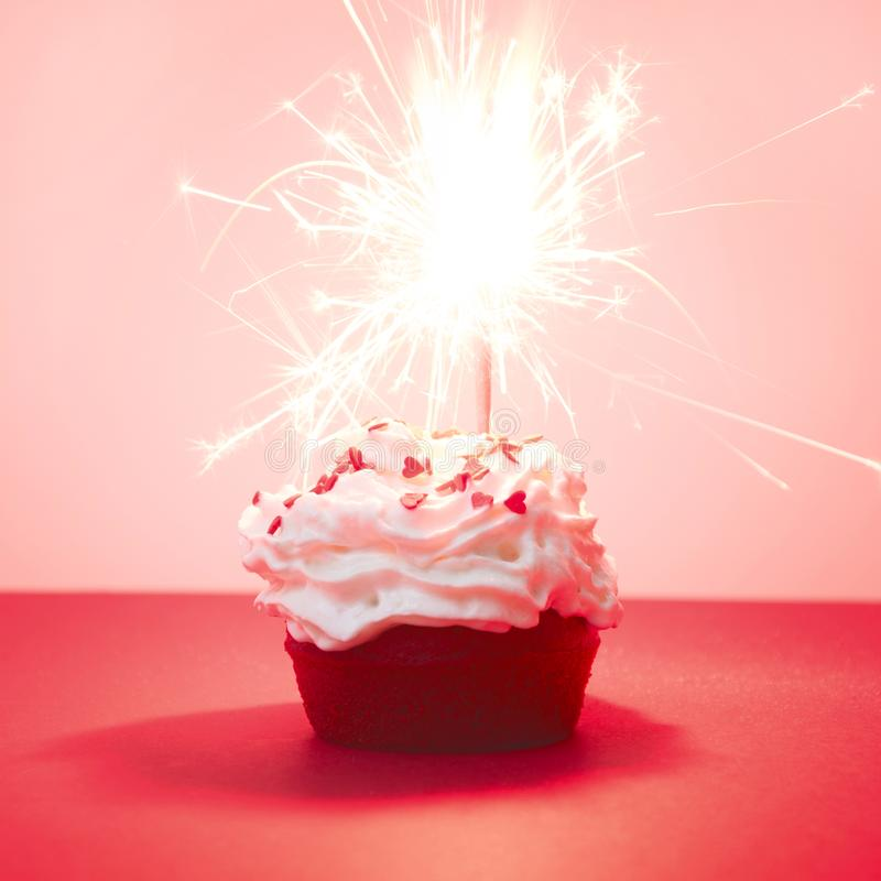Red velvet cupcake with bengal lights on red background, red muffin. Square image. Valentine`s or birthday card. Magic sparks lig stock photography