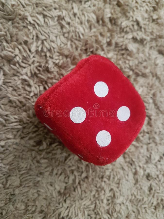 Red Velvet dice with number four to play stock photos