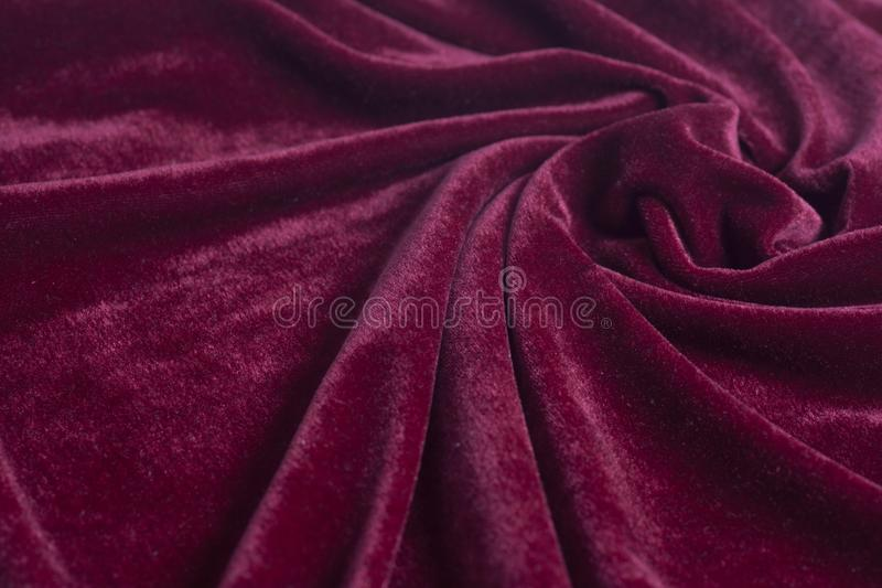 Red velvet fabric with spiral folds stock images