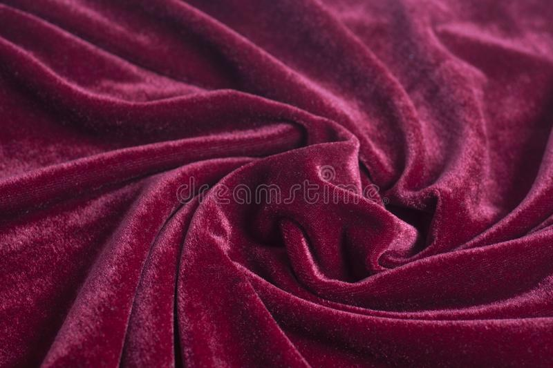 Red velvet fabric with spiral folds royalty free stock photos