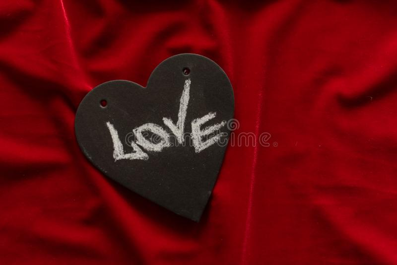 Red velvet, fabric texture and black heart with love inscription stock image