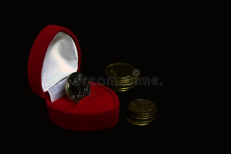 Red velvet gift box with a coin instead of a ring on a black background with coins of different denominations symbolizing a marri royalty free stock photography