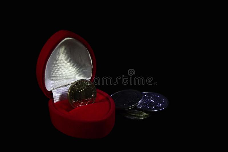 Red velvet gift box with a coin instead of a ring on a black background with coins of different denominations symbolizing a marria stock photo