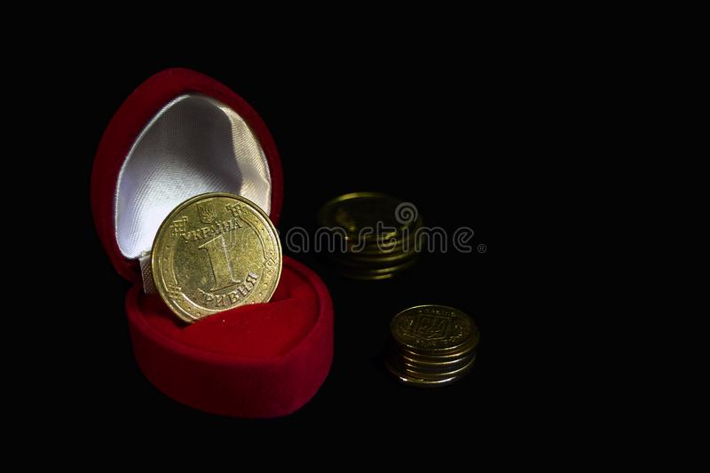 Red velvet gift box with a coin instead of a ring on a black background with coins of different denominations symbolizing a marria royalty free stock images
