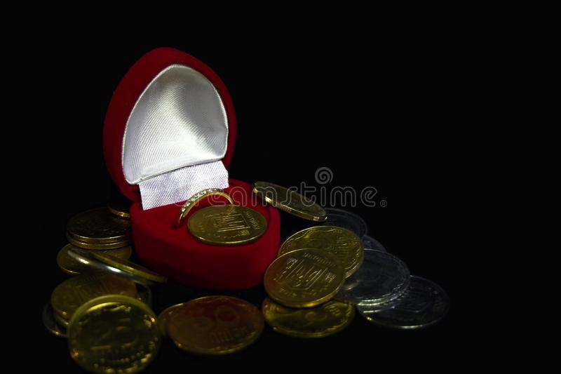 Red velvet gift box with a gold ring and diamonds on a black background with coins of different denominations, symbolizing a marr stock photography