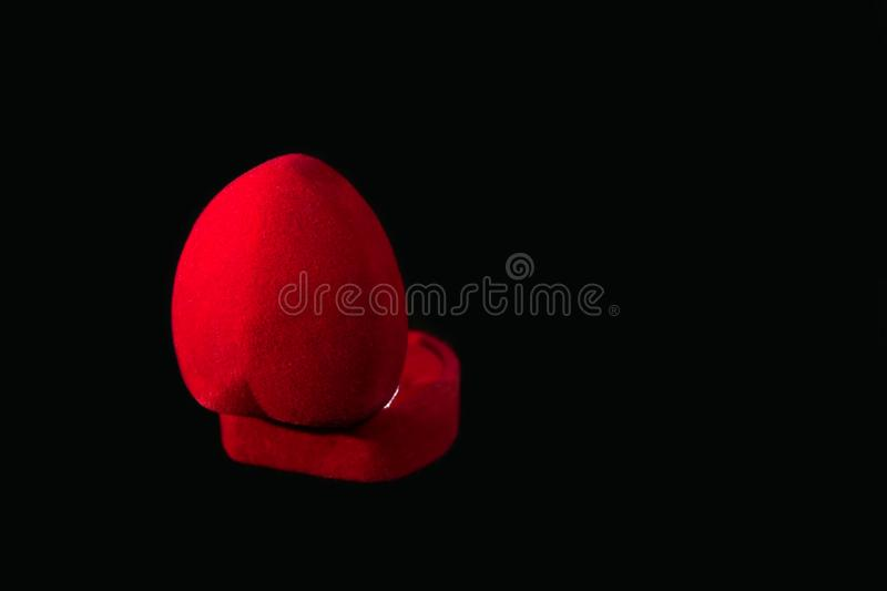 Red velvet gift box for a ring on a black background royalty free stock image