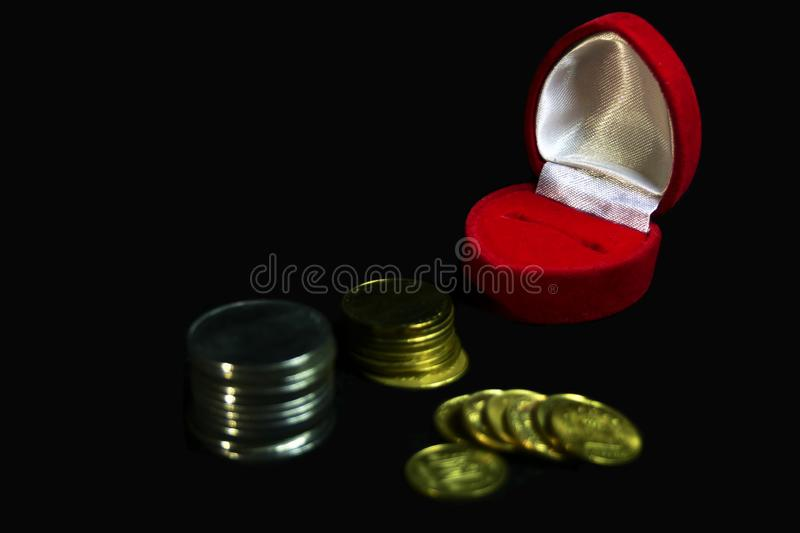Red velvet gift box for a ring on a black background with coins of different denominations, symbolizing a marriage of convenience, stock images