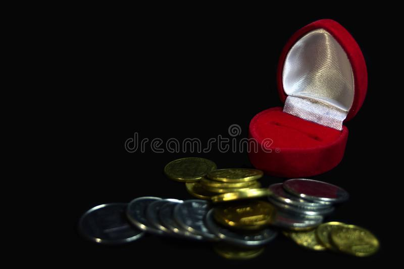 Red velvet gift box for a ring on a black background with coins of different denominations symbolizing a marriage of convenience,. Selling love or love of money royalty free stock image