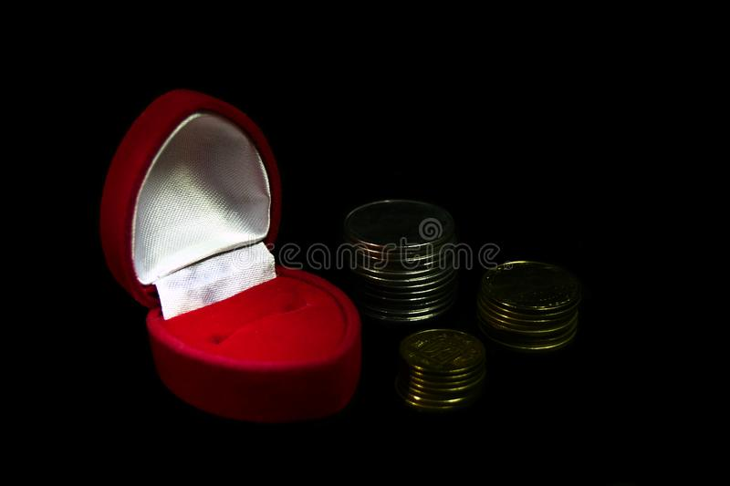 Red velvet gift box for a ring on a black background with coins of different denominations symbolizing a marriage of convenience, royalty free stock photos