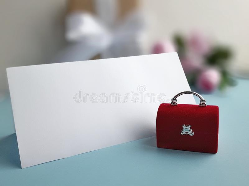 Red velvet jewelry chest with blank folded card on blue background. Wedding holiday concept. stock images