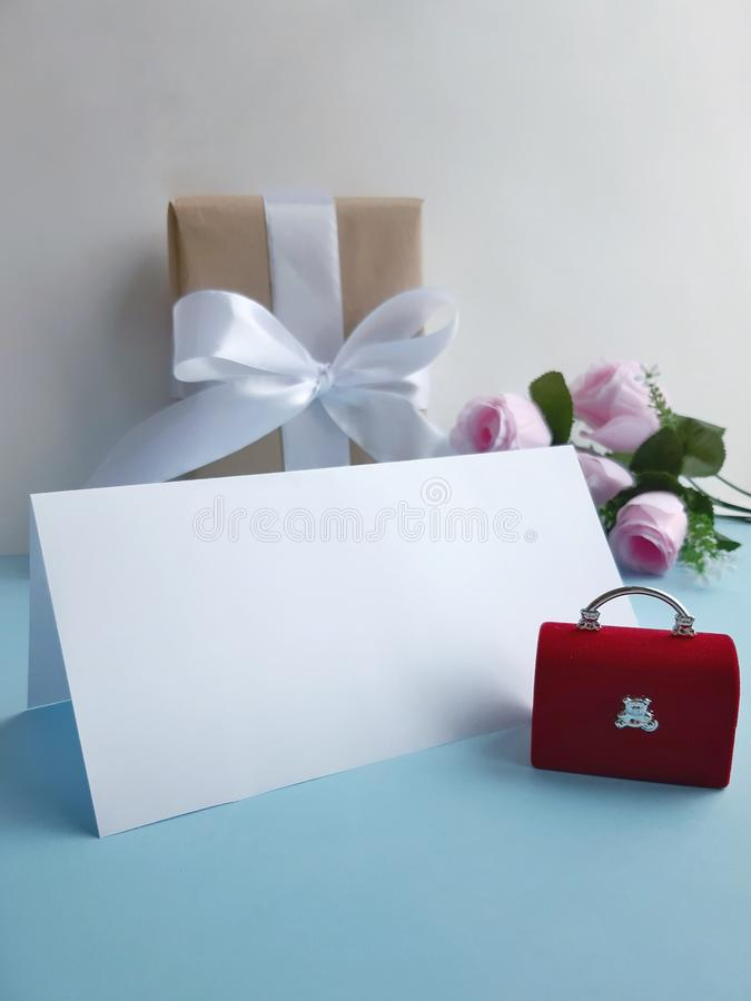 Red velvet jewelry  chest with blank folded card, gift box, roses on blue background. royalty free stock photo