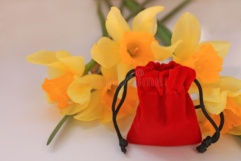Red velvet pouch with yellow flowers on a white background isolated royalty free stock images