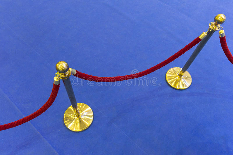 Red velvet rope and a blue carpet. Abstract background royalty free stock images