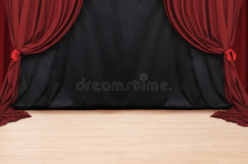 Red Velvet Theater. Stage of red theatery drapery with black background and wooden floor royalty free stock photography