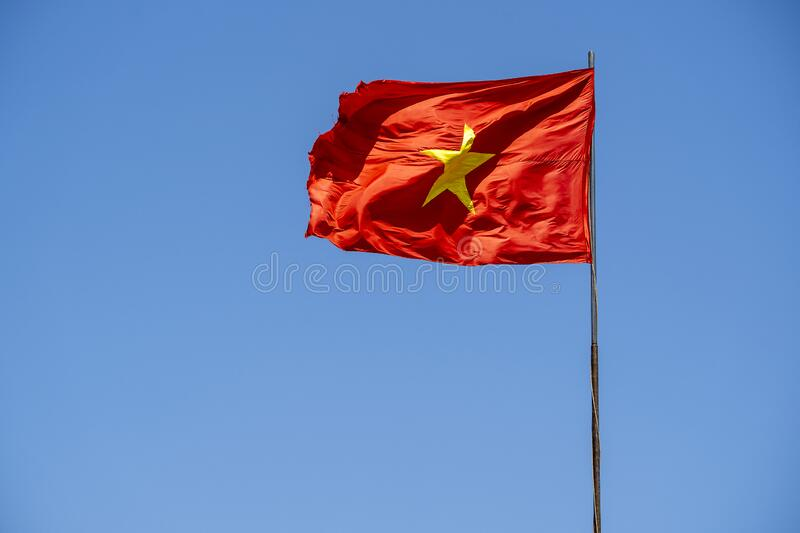 Red Vietnam flag against the blue sky. Close up stock images