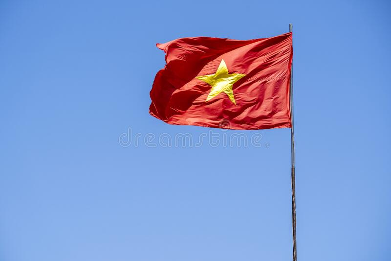 Red Vietnam flag against the blue sky. Close up royalty free stock photo